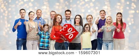 sale, shopping, family, generation and people concept - group of happy men and women showing thumbs up and percent sign over holidays lights background