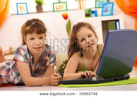 Grundschulkind Mädchen Spiel Computer auf Laptop zu Hause, Blick in die Kamera Lächeln.