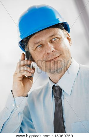 Portrait of architect talking on mobile, looking at camera, smiling.