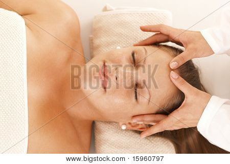 Young woman getting relaxing head massage in day spa, smiling.