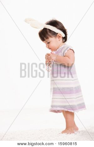 Profile portrait of baby girl in easter costume standing on carpet, holding easter eggs, looking down. Isolated on white background.