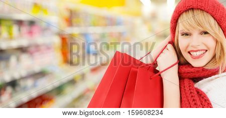 people, winter holidays, sale and consumerism concept - happy smiling woman in red hat and scarf with many shopping bags over supermarket background