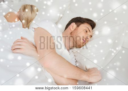people, health, sleep disorder concept - couple lying in bed at home and young man suffering from insomnia over snow