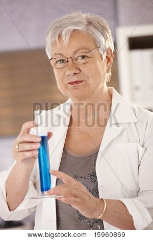 Senior teacher standing in classroom, holding test tube, teaching chemistry in elementary school.?