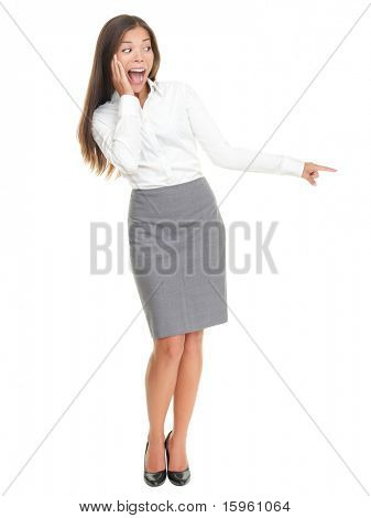 Surprised woman pointing. Pretty businesswoman standing in full length isolated on white background.