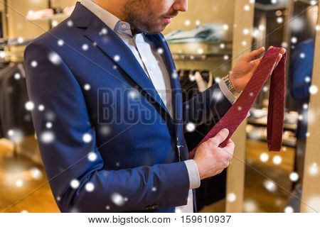 sale, shopping, fashion, style and people concept - elegant young man choosing and trying tie on at clothing store over snow