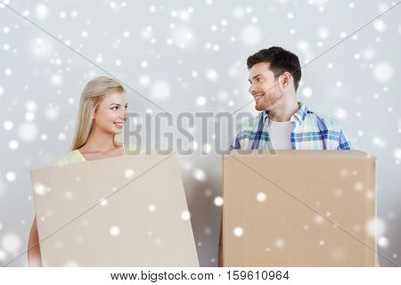 home, people and real estate concept - smiling couple with big cardboard boxes moving to new place over snow