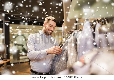 sale, shopping, fashion, style and people concept - happy young man in shirt choosing jacket in mall or clothing store over snow