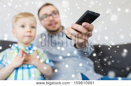 family, childhood, fatherhood, technology and people concept - happy father and little son with remote control watching tv at home over snow