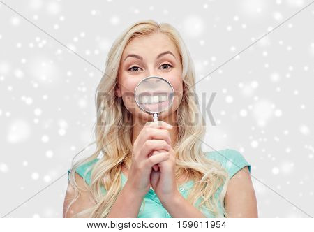 fun, emotions, expressions and people concept - happy smiling young woman or teenage girl with magnifying glass making face  over snow