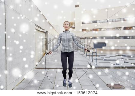 fitness, sport, people, exercising and healthy lifestyle concept - woman skipping with jump rope outdoors over snow