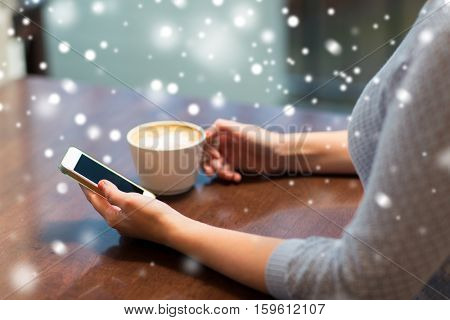 drinks, people, technology and communication concept - young woman with smartphone drinking coffee at cafe over snow
