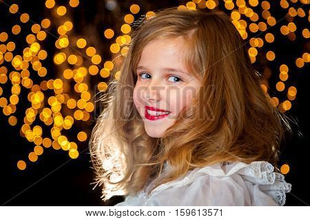 A beautiful blond little girl smiles for the camera against a starry background. She is smiling and wearing puffed sleeves.