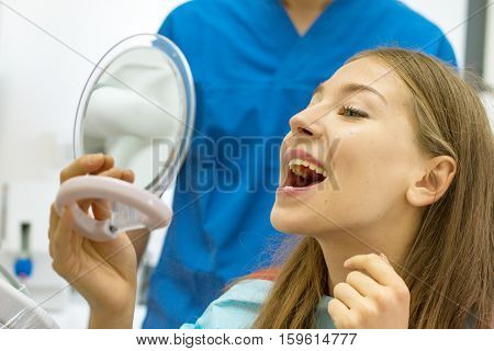 woman with beautiful white teeth at dental clinic examines her teeth using the mirror during checkup by the dentist who stands defocused in background