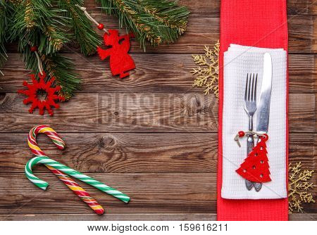 Christmas table place setting with fork and knife, decorated christmas toy - red fir-tree, christmas pine branches and two lollipop cane. Christmas holidays background.