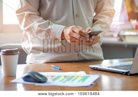 Man office staff using smart phone with analyzing graphs.