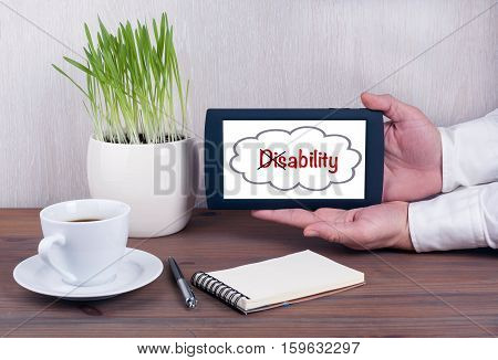 Turning the word Disability into Ability. Digital tablet computer with isolated screen in male hands.