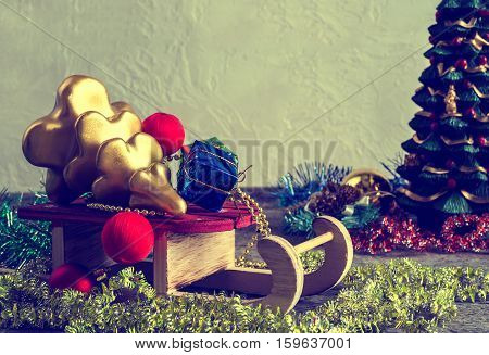 Christmas tree and gift boxes sleigh with presents on an old wooden surface space for text retro style