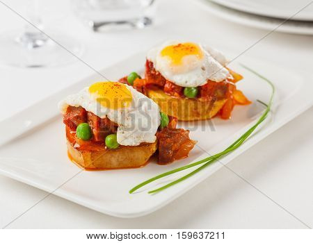 Chorizo and fried egg on a potato slice. Small plate for sharing.