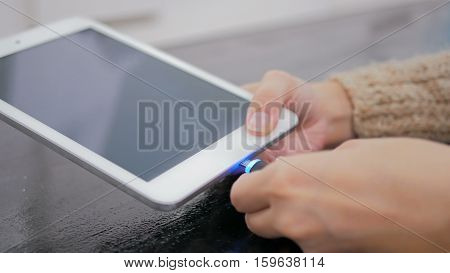 Woman's hand plugging black lightning charging cable into pc digital tablet - USB data cable connecting on modern gadget. Close up