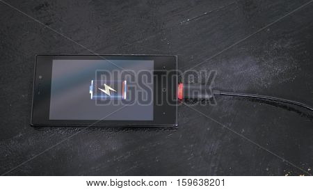 Smartphone with low battery icon on screen - USB data cable connecting on modern gadget. Close up