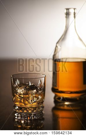 Whiskey with ice in glass and bottle on wooden background