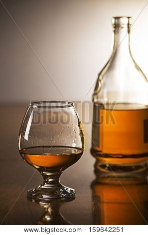 Cognac in glass with bottle on wooden table