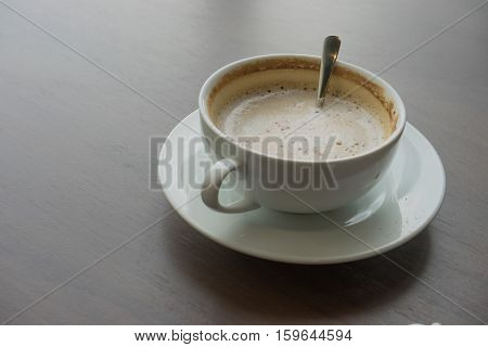 hot coffee in white cup white foam with silver spoon on wooden table at coffee time sunset / hot coffee