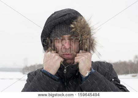 Man covering under the hood from a snowstorm head and shoulders outdoor portrait