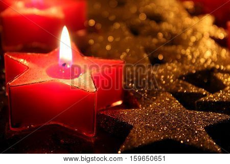 This photo is part of a series of personal experiments on the light that I am making using elements reminiscent of Christmas items. Candles and decorations used are red and glittery golden color and have the star shape.