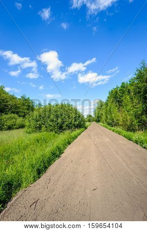 Colorful Dutch landscape on a hot day at the end of the spring season with a bright blue sky and white clouds. The straight road of loose sand is seemingly endless.