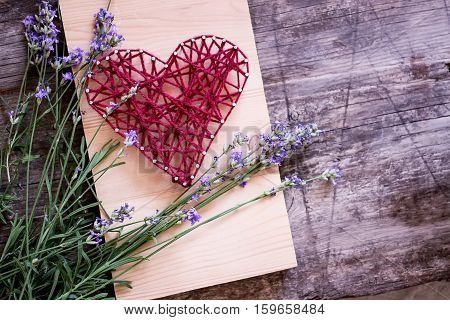 Heart shape of the threads on wood desk with lavender. Flat layout