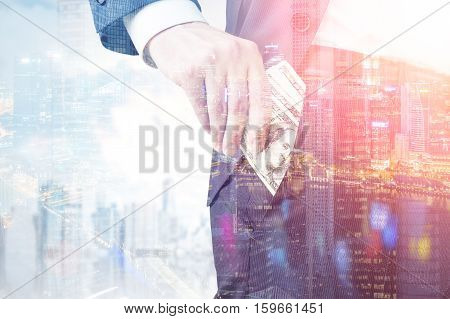 Close up of a businessman putting a pack of money into his pocket. Large city is seen in the background. Concept of bribery. Toned image. Double exposure.