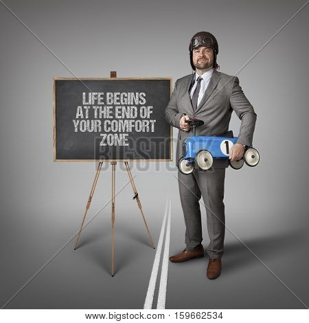 Life begins at the end of your comfort zone text on blackboard with businessman and toy car