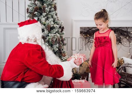 Santa Claus and children opening presents at fireplace. Kids father in costume wearing beard open Christmas gifts. Little girl helping with present sack. Family under Xmas tree over fire place on background