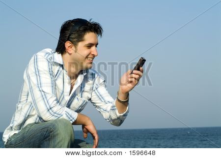 Young Man Reading A Message On His Mobile