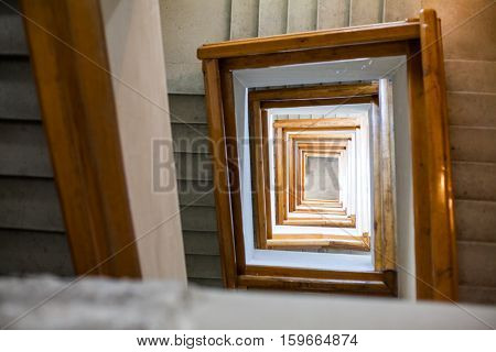 Color image of a spiral square staircase in a building.