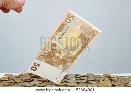 Banknote of 50 Euros standing over Euro coins.