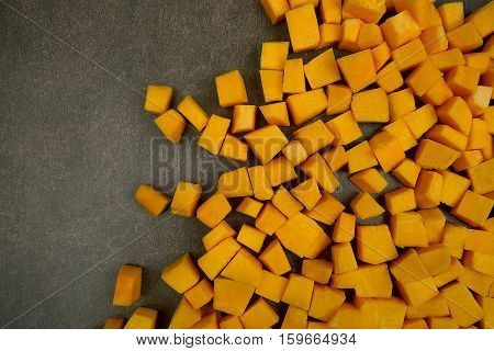 Pupkin cubes on stone background. Pupkins cubes arranged in right side.