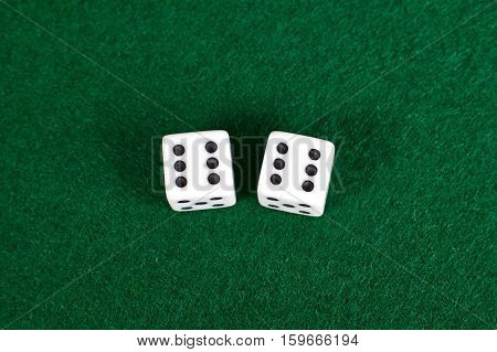 White dices close up view  green table.