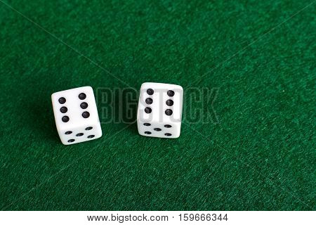 White dices closeup view on green table.