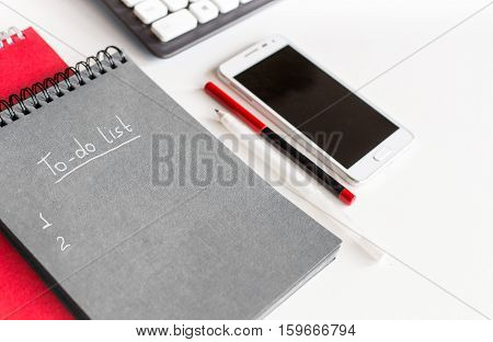 to-do list in a notebook on the office desk with mobile phone