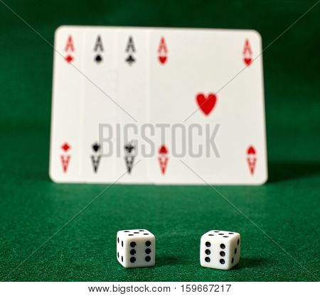 White dices and four aces on green table.Illegal gambling.