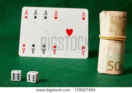 White dices four aces and a roll of money on agreen table.Illegal gambling.