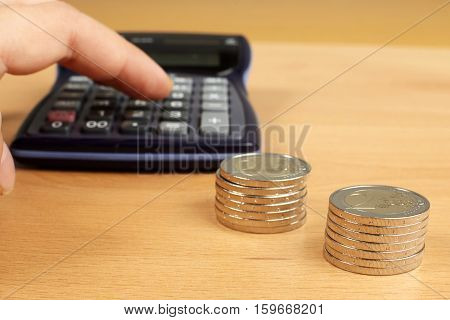 Hand with calculator and money on wooden table.