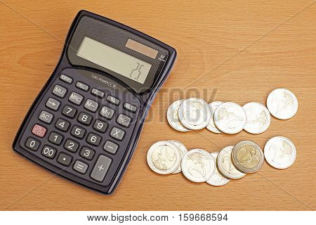 Euro coins and calculator on wooden table.