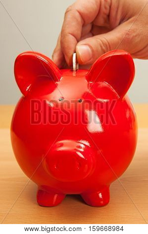 Hand put a coin in a red piggy bank.