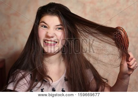beautiful teen girl try comb her long dark thick hair