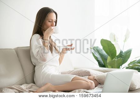 Young woman wearing a dressing gown, having a pleasant beginning of day drinking coffee looking at the laptop, conducting business online, resting in a hotel room, enjoying movie