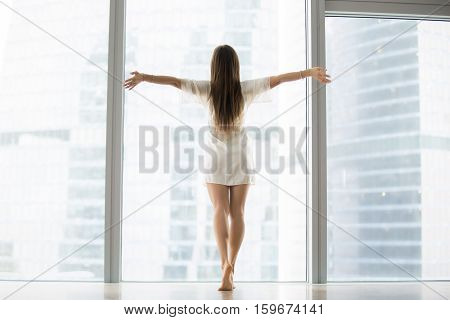 Young model in modern high rise building room with full length windows, outstretching arms, welcoming new day, dancing bare foot in morning, bought new flat. Feeling happy, alive, dreaming. Rear view